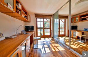 Pracovna ze světlého dřeva s velkým pracovním stolem a úložným prostorem