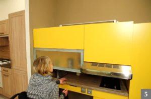 Paní na invalidním vozíku v bezbariérové kuchyni