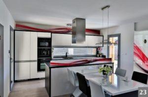 Nadčasová kuchyně s výraznými dekorativními prvky a jídelním stolem