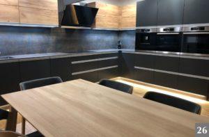 Tmavá kuchyně s dřevěnými prvky a kovovými úchyty